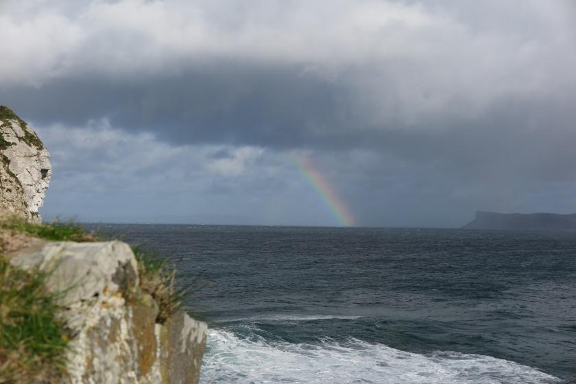 遠足時遠望大海,陰雲下散出一道彩虹